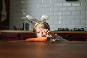 boy grabbing carrot on table